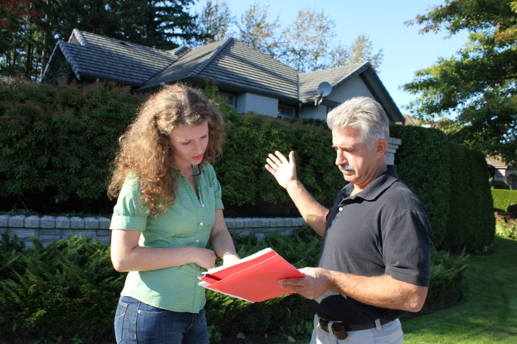 man and woman in front of a property